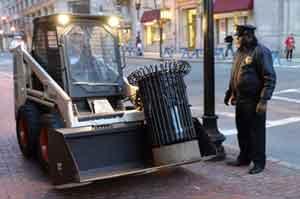 Un policía observa la retirada de un cubo de basura de la zona donde se registraron las explosiones. | Efe