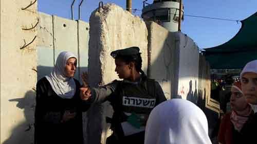 Una policía palestina indica el camino a una mujer palestina antes de cruzar el paso fronterizo de Kalandia hasta Jerusalén, en Cisjordania. EFE/Archivo