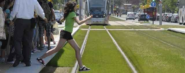Una joven cruza las vías imprudentemente con un Urbos a punto de pasar.