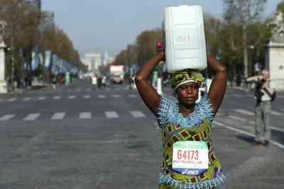 Una mujer africana con un cubo recorre el maratón de París