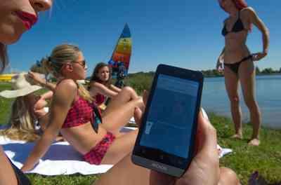Una modelo muestra su smartphone con la interfaz conectado a su traje de baño